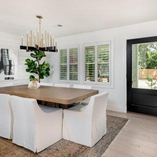 Réalisation d'une grand salle à manger tradition avec un mur blanc, un sol en bois clair, un sol beige et du lambris de bois.