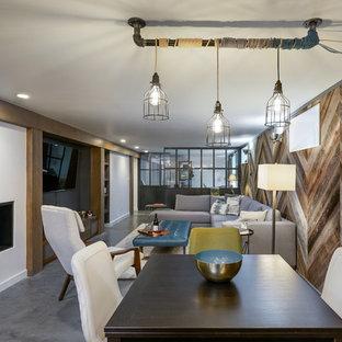 Foto di una sala da pranzo aperta verso il soggiorno industriale con pavimento in cemento, camino classico, pavimento grigio e pareti bianche
