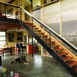 Idee per una piccola sala da pranzo aperta verso il soggiorno industriale con pareti gialle e pavimento in cemento