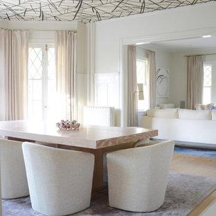 Immagine di una grande sala da pranzo aperta verso il soggiorno contemporanea con pareti bianche, parquet chiaro, camino classico, cornice del camino in cemento e pavimento beige