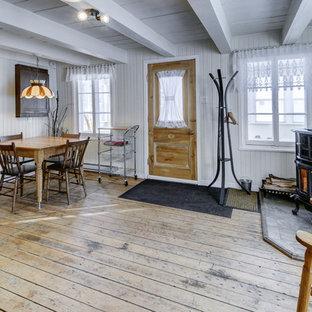 Modelo de comedor de cocina rústico, pequeño, con paredes blancas, suelo de madera clara, estufa de leña y marco de chimenea de baldosas y/o azulejos