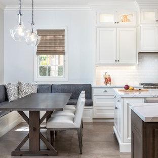 Imagen de comedor de cocina mediterráneo, grande, con paredes blancas, suelo de baldosas de porcelana, chimenea de doble cara, marco de chimenea de madera y suelo marrón