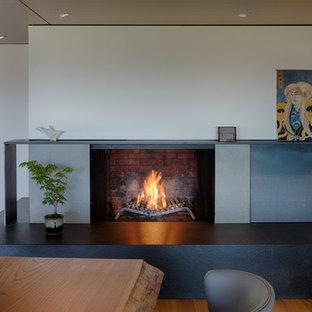 Modelo de comedor de cocina moderno, de tamaño medio, con paredes grises, suelo de madera en tonos medios, chimenea de esquina, marco de chimenea de hormigón y suelo marrón