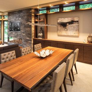 Modelo de comedor moderno, pequeño, abierto, con paredes beige, suelo de cemento y marco de chimenea de piedra