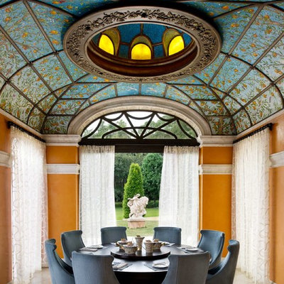 Enclosed dining room - mediterranean travertine floor and brown floor enclosed dining room idea in Orlando with orange walls and no fireplace