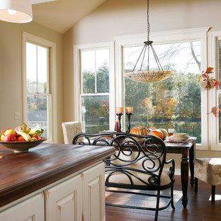 Idee per una sala da pranzo aperta verso la cucina chic di medie dimensioni con pareti beige, parquet scuro, nessun camino e pavimento marrone