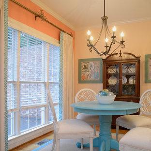 Idee per una piccola sala da pranzo aperta verso il soggiorno country con pareti arancioni, parquet chiaro e nessun camino