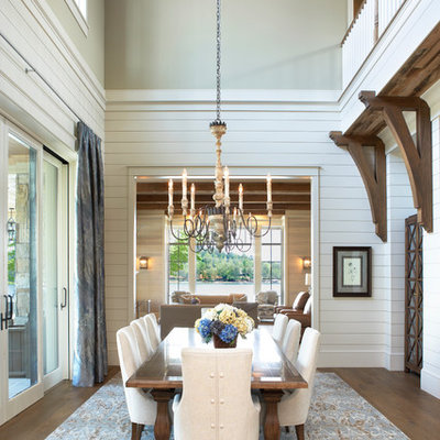 Example of a beach style medium tone wood floor and brown floor dining room design in Other with white walls