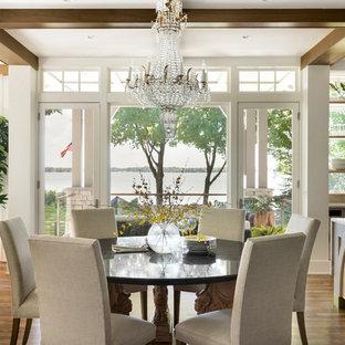 Immagine di una sala da pranzo aperta verso la cucina country con pareti bianche, pavimento in legno massello medio e pavimento marrone