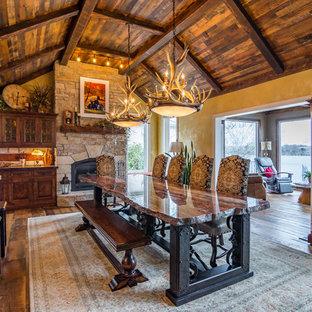 Ejemplo de comedor de cocina rural, extra grande, con paredes amarillas, chimenea tradicional y marco de chimenea de piedra