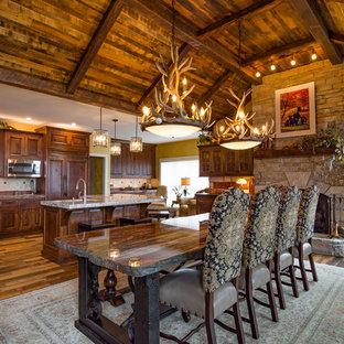 Источник вдохновения для домашнего уюта: большая кухня-столовая в стиле рустика с желтыми стенами, паркетным полом среднего тона, стандартным камином и фасадом камина из камня