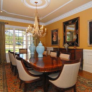 Foto di una grande sala da pranzo classica chiusa con pareti arancioni, parquet scuro, nessun camino e pavimento marrone