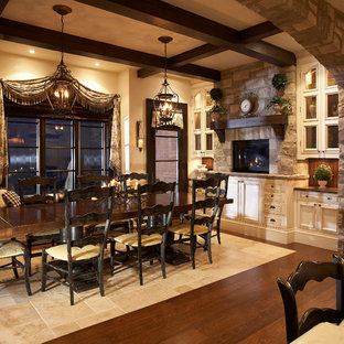 Example of a large classic medium tone wood floor kitchen/dining room combo design in Toronto with beige walls, a stone fireplace and a wood stove