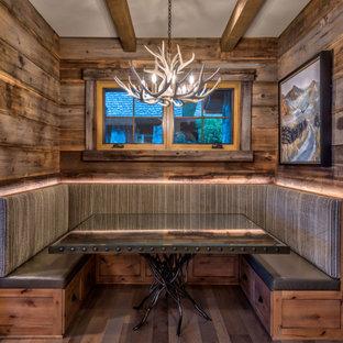 Imagen de comedor de estilo americano, de tamaño medio, con paredes grises, suelo de madera en tonos medios, chimenea de doble cara, marco de chimenea de piedra y suelo marrón