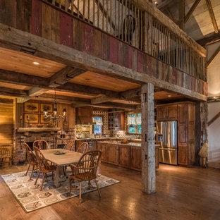 Ejemplo de comedor rústico, abierto, con suelo de madera en tonos medios, chimenea tradicional y marco de chimenea de ladrillo