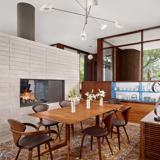 This is an example of a midcentury dining room in Austin with a two-sided fireplace.