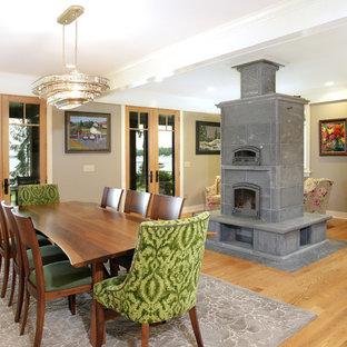 Diseño de comedor de estilo americano, abierto, con paredes grises, suelo de madera clara, chimenea tradicional, marco de chimenea de baldosas y/o azulejos y suelo marrón