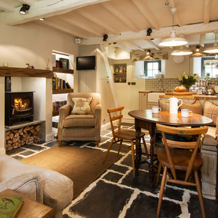 Immagine di una piccola sala da pranzo country con pareti beige, stufa a legna, cornice del camino in intonaco e pavimento nero