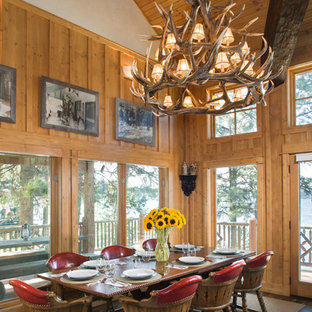 This is an example of a large country open plan dining in Boise with brown walls and medium hardwood floors.