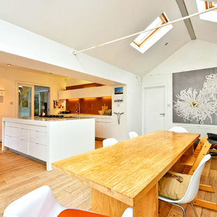 Large contemporary kitchen/dining room in Sussex with white walls, light hardwood flooring, no fireplace and beige floors.