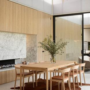 メルボルンのコンテンポラリースタイルのおしゃれなダイニング (ベージュの壁、横長型暖炉、グレーの床) の写真