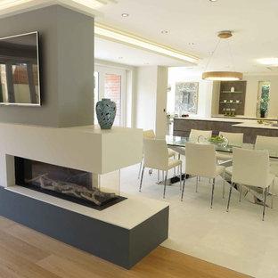 Ejemplo de comedor moderno, de tamaño medio, abierto, con chimenea de doble cara, paredes blancas, suelo blanco, suelo de cemento y marco de chimenea de hormigón