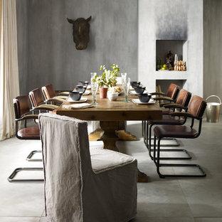 Imagen de comedor de cocina bohemio, grande, con paredes multicolor, suelo de cemento, chimenea tradicional y marco de chimenea de yeso