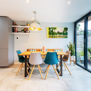 Photo of a scandi kitchen/dining room in London with white walls and beige floors.