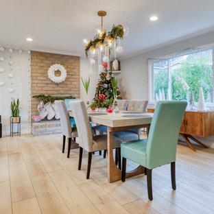 Cette image montre une salle à manger ouverte sur le salon vintage de taille moyenne avec un mur gris, un sol en vinyl, une cheminée standard, un manteau de cheminée en brique et un sol jaune.
