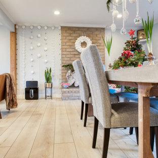 Cette photo montre une salle à manger ouverte sur le salon rétro de taille moyenne avec un mur gris, un sol en vinyl, une cheminée standard, un manteau de cheminée en brique et un sol jaune.