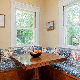 Foto di una piccola sala da pranzo aperta verso la cucina tradizionale con pareti gialle e nessun camino