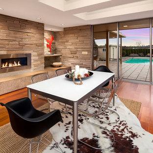 Новые идеи обустройства дома: столовая в стиле ретро с бежевыми стенами, паркетным полом среднего тона, камином, фасадом камина из металла и коричневым полом