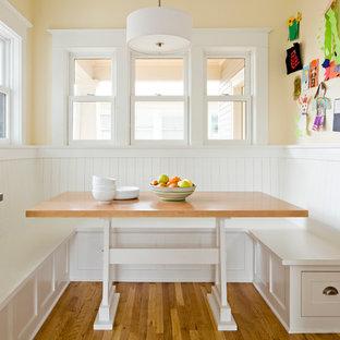 Ejemplo de comedor de cocina clásico, pequeño, sin chimenea, con paredes amarillas, suelo de madera en tonos medios y suelo marrón