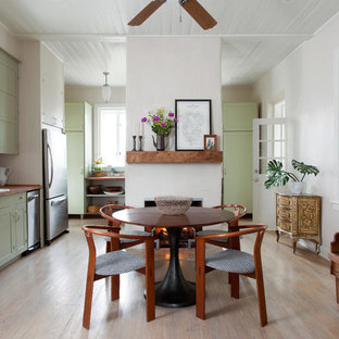 Kitchen/dining room combo - mid-sized farmhouse light wood floor and beige floor kitchen/dining room combo idea in Austin with white walls, a standard fireplace and a plaster fireplace