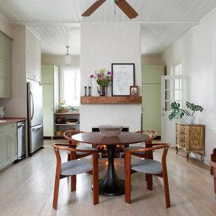 Diseño de comedor de cocina de estilo de casa de campo, de tamaño medio, con paredes blancas, suelo de madera clara, chimenea tradicional, marco de chimenea de yeso y suelo beige