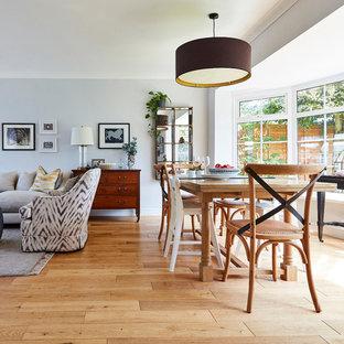 Aménagement d'une salle à manger ouverte sur le salon classique de taille moyenne avec un mur blanc, un sol en bois brun, une cheminée standard, un manteau de cheminée en pierre et un sol jaune.