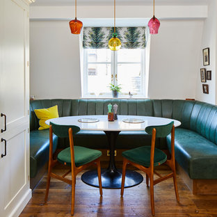 Inspiration for an eclectic dining room in London with white walls, medium hardwood flooring and brown floors.