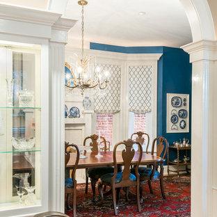 Inredning av en klassisk stor separat matplats, med blå väggar, mörkt trägolv, en standard öppen spis, en spiselkrans i trä och brunt golv