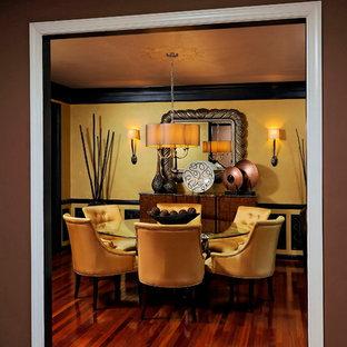 Esempio di una sala da pranzo contemporanea chiusa e di medie dimensioni con pareti gialle, parquet scuro e nessun camino