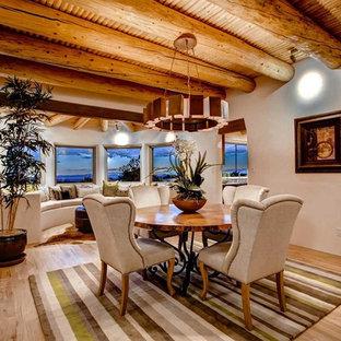 Imagen de comedor de estilo americano, abierto, con suelo de madera clara y paredes beige