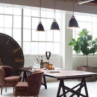 Ispirazione per un'ampia sala da pranzo aperta verso il soggiorno industriale con pareti bianche, pavimento in cemento e nessun camino