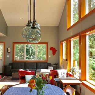 Imagen de comedor ecléctico, de tamaño medio, abierto, con paredes grises, suelo de corcho, estufa de leña, marco de chimenea de baldosas y/o azulejos y suelo marrón