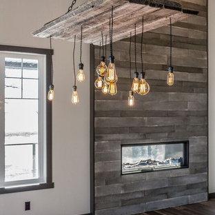 Foto di una grande sala da pranzo aperta verso la cucina country con pavimento in vinile, camino bifacciale, cornice del camino in cemento e pavimento grigio