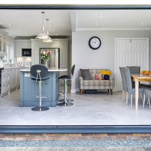 This is an example of a large traditional grey and white single-wall kitchen/diner in Other with grey floors, a built-in sink, shaker cabinets, grey cabinets, engineered stone countertops, white splashback, ceramic splashback, black appliances, ceramic flooring, an island and white worktops.