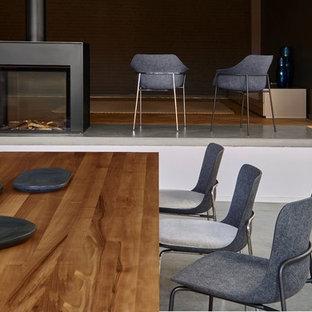 Esempio di una grande sala da pranzo aperta verso il soggiorno minimalista con pavimento in legno massello medio, camino sospeso e cornice del camino in metallo
