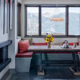 Imagen de comedor rural con paredes grises, suelo de cemento, chimenea de doble cara, marco de chimenea de metal y suelo gris