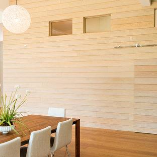 Immagine di una grande sala da pranzo aperta verso la cucina minimalista con pareti beige, pavimento in legno massello medio, camino classico, cornice del camino in pietra e pavimento beige