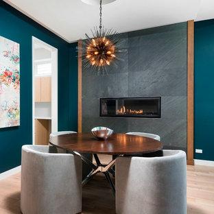 Imagen de comedor contemporáneo, de tamaño medio, con suelo de madera clara, chimenea lineal, paredes azules y marco de chimenea de baldosas y/o azulejos