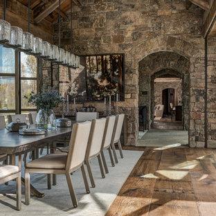 Immagine di una grande sala da pranzo aperta verso il soggiorno rustica con pareti marroni, parquet scuro e nessun camino