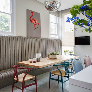 Immagine di una sala da pranzo aperta verso la cucina contemporanea con pareti beige e pavimento in cemento